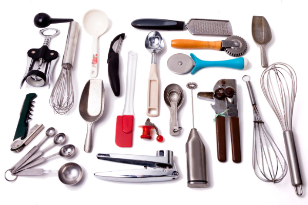 a flat lay image of an assortment of manual kitchen tools like a garlic press, vegetable peeler, mini whisk, ice cream scoop and more