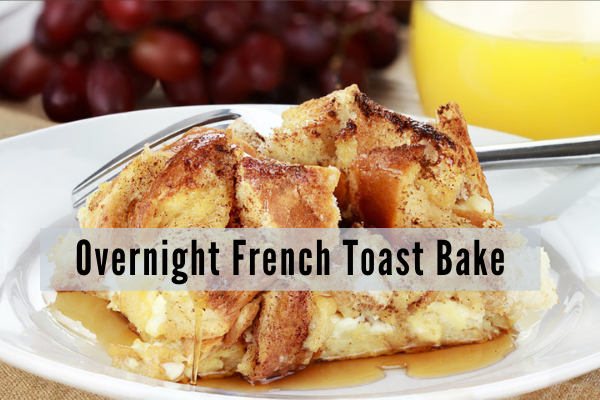 a plate with soft eggy french toast cubes drizzled with maple syrup with a glass of orange juice and red grapesin the background
