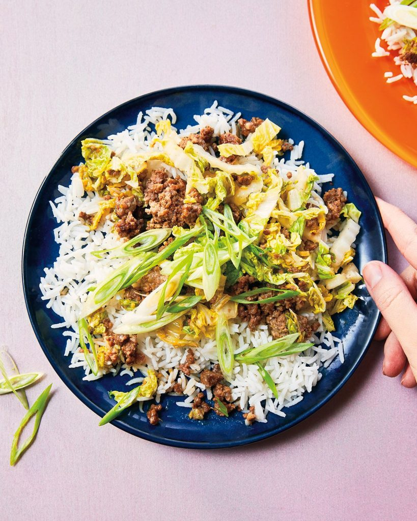a dark blue plate with rice, ground beef in a dark sticky sauce and sliced scallions