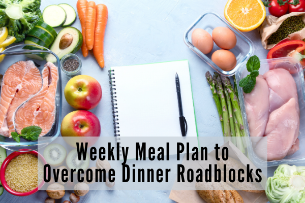 A weekly meal plan journal on a table along with various ingredients to be used during the week