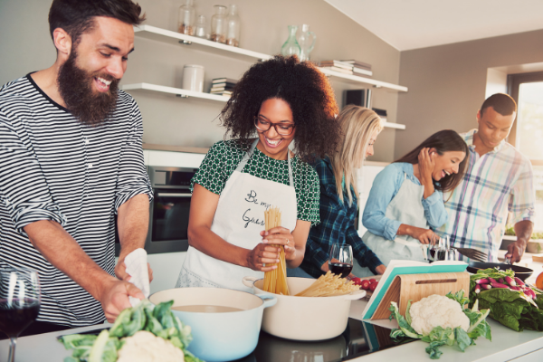 family of diverse young adults cooking a spagheti supper together