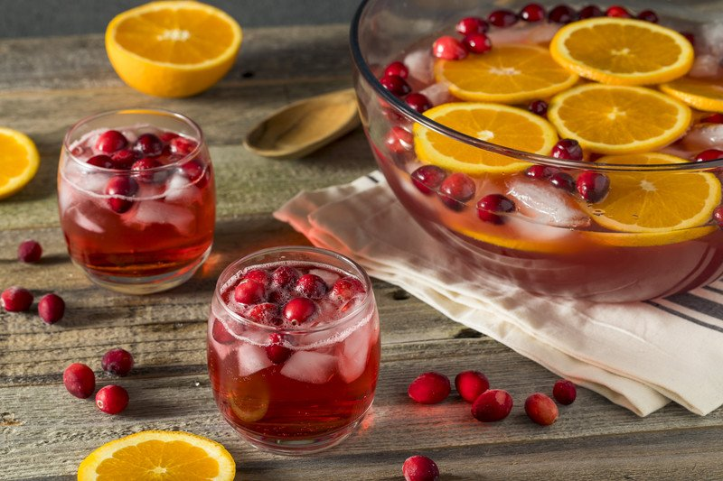 a bowl of red punch that has orange slices and cranberries floating in it
