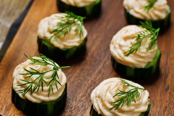 cucumbuer rounds topped with a piped salmon spread and sprigs of dill