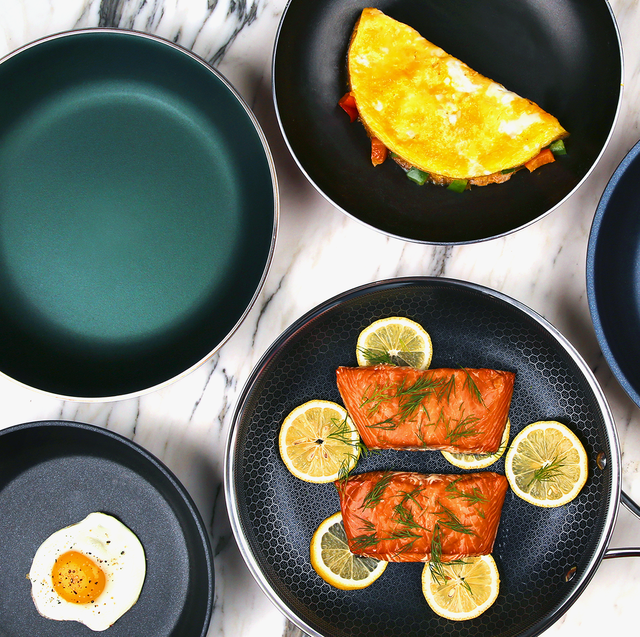 Four non stick pans shot from above. One is empty, one contains samlon fillets and lemon slices, one contains an omelette, and one a fried egg