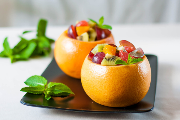 a fruit salad served in a hollowed grapefruit