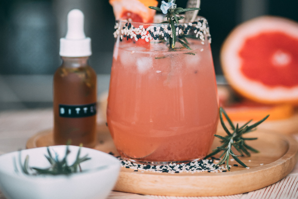 a pale pink negroni cocktail is displayed with bitters in a dropper bottle and rosemary sprigs