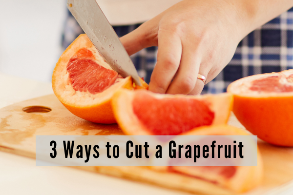 A man wearing plaid pajama bottoms clices a grapefruit at the kitchen counter