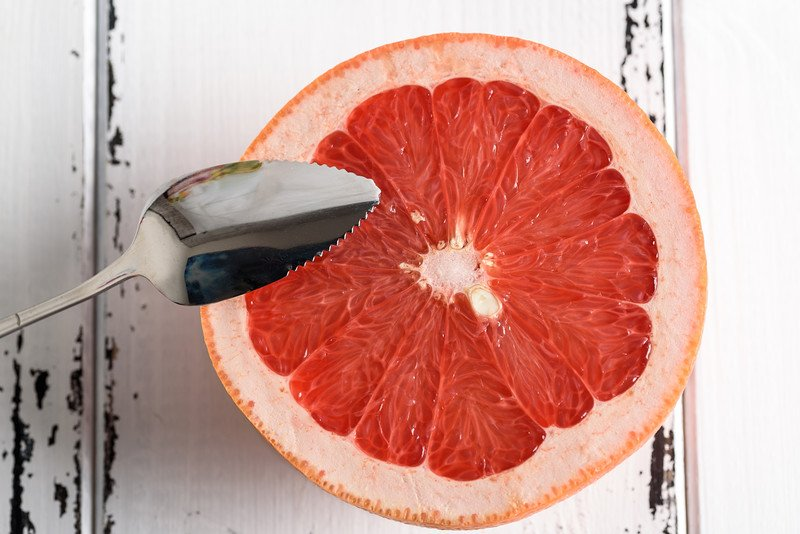 A half grapefruit shown flesh side up with a silver serrated grapefruit spoon about to dig in