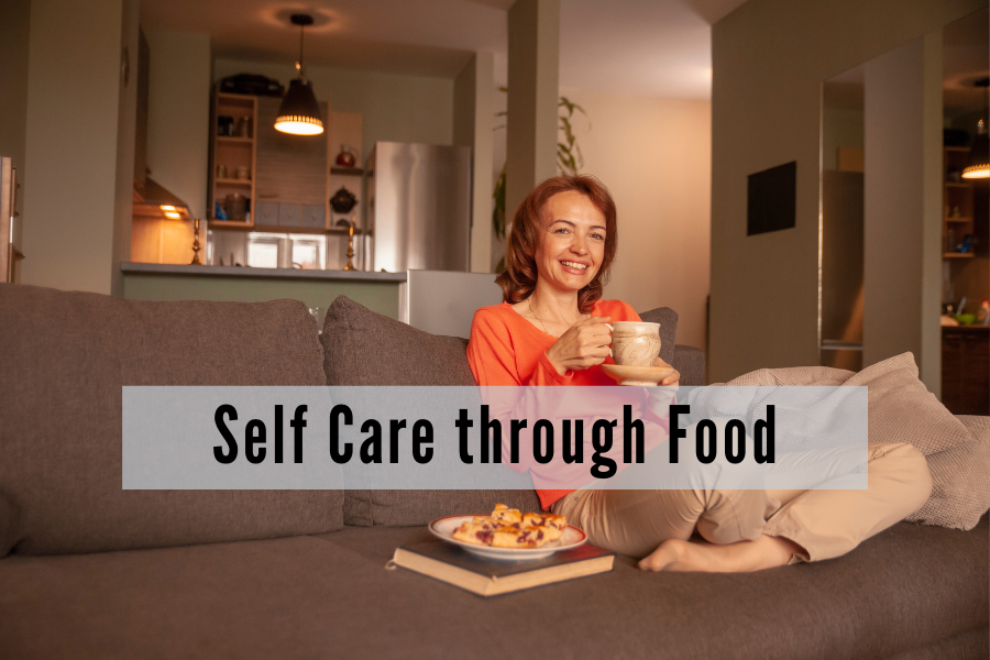 a middle aged woman sits on a couch cross legged drinking a cup of tea