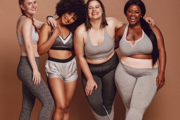 four young women of a variety of body shapes and skin colours laugh together while wearing workout wear