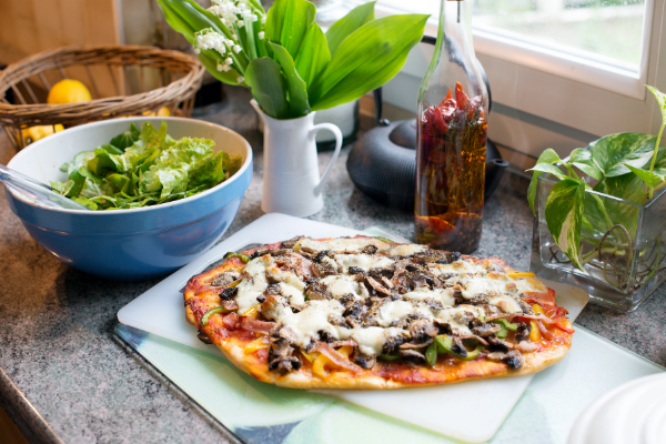 a small flabread pizza sits next to fresh herbs and a bowl of green salad in a sunny spot on a table