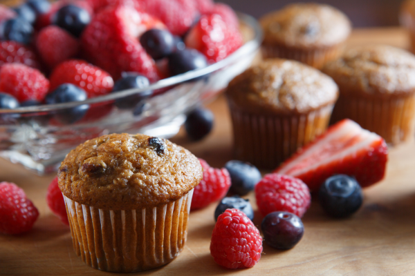 golden brown muffin with berries in a white liner next to a plate of fresh raspberries, blueberries and strawberries