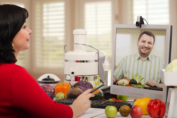 a woman takes notes while talking virtually with a registered dietitian. She has a juicer and a variety of fruts on her desk.