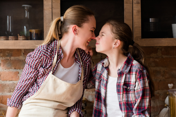 A nother and daughter stand in a kitchen looking at each other. Their noses are touching. It is a very loving image.