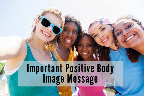 four young girls with their arms around each other smile for a picture ouside on a sunny day