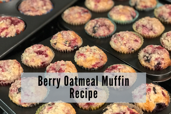muffin tins containing golden oatmeal muffins with juicy pink berries