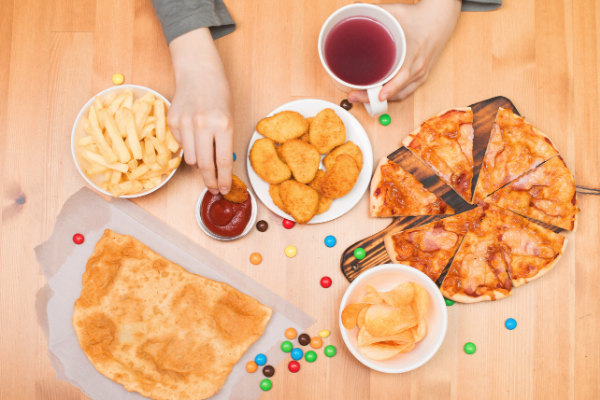a variety of fast food sits on a table including pizza, wings and french fries