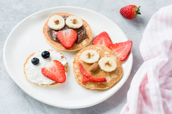pancakes topped with cream cheese, nutella bananas and fruit to look like cute faces