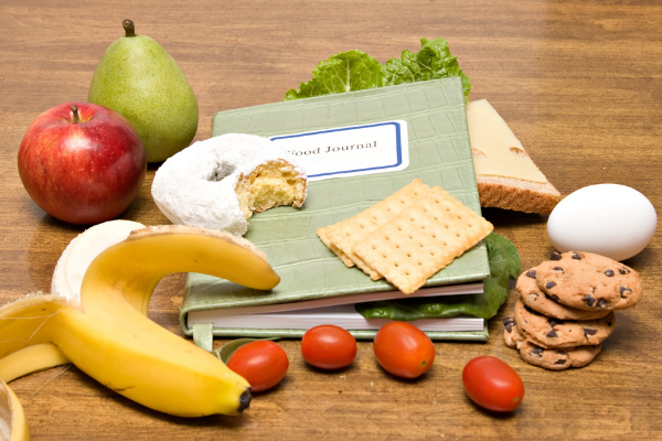 a notebook labelled food diary on a table with a pear, banana and cherry tomatoes
