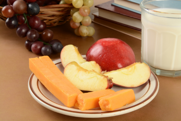 a plate with sliced red apple and slices of cheddar cheese with red grapes on the side
