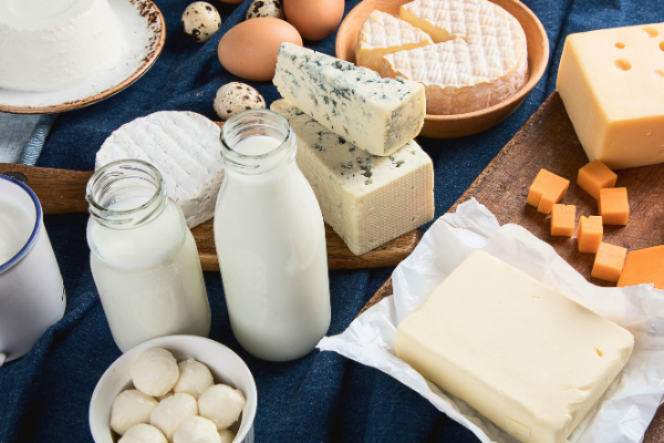 a collage of foods containing calckum including glass bottles of milk, cheese and butter