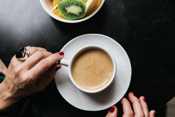 an overhead shot of a woman with red nail polish stirring a cup of coffe on a saucer. A plate of fruit is above the coffee.