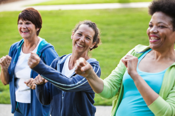 three mature women exercising outdoors and smiling