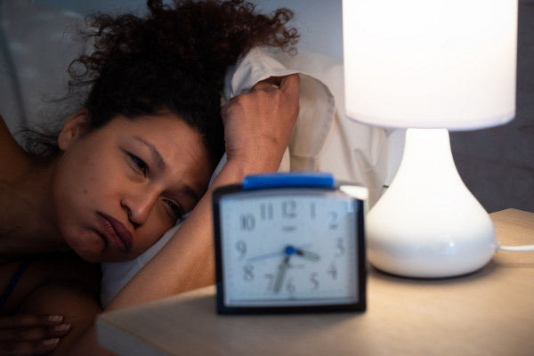 a tired woman with dark curly hair lies in bed frowning at her clock