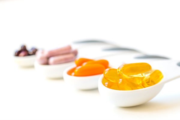 three small bowls of colourful gel capsules on a white background