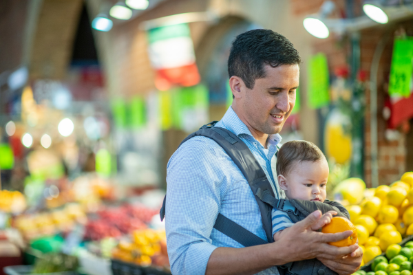 dad grocery shopping for fruit with baby in a front baby carrier