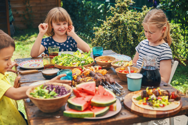 Family eating a meal outside at a picnic table covered in dishes like watermelon slices, salads and chicken skewers