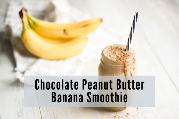 a chocolately smoothie in a mason jar with a metal straw sits in front of a bunch of bananas