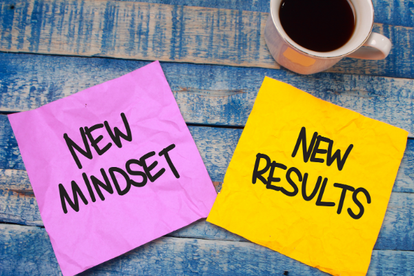 new mindset is written on a pink post it note, new results is written on a yellow post it note next to each other