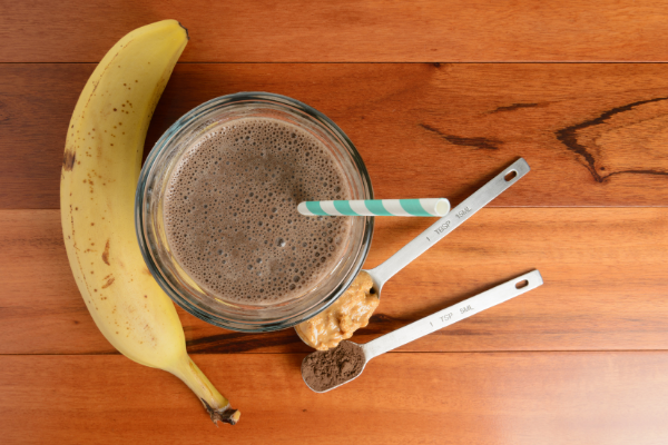 a chocolate smoothie shot from above with a banna and spoonful of peanut butter and cocoa powder arranged beside it