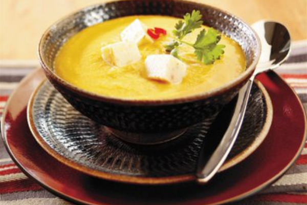 a round brown bowl filled with yellow lentil soup topped with cilantro and cubes of cheese