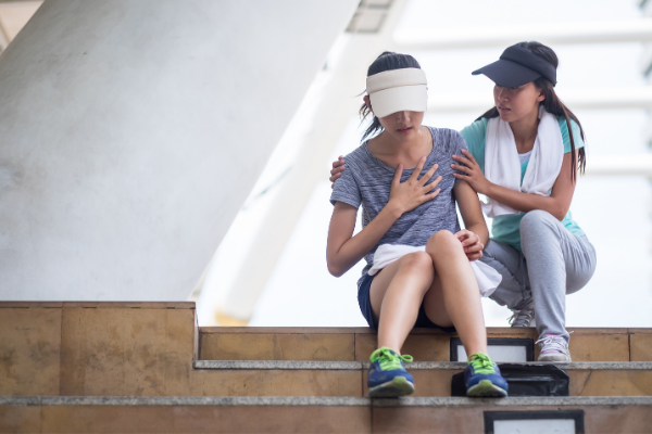 two women sit on gym stairs, one supporting the other who looks weak and tired
