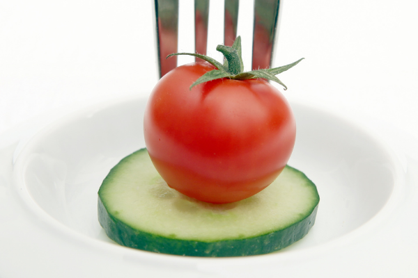 cucumber and cherry tomato on a small white plate being speared with a fork