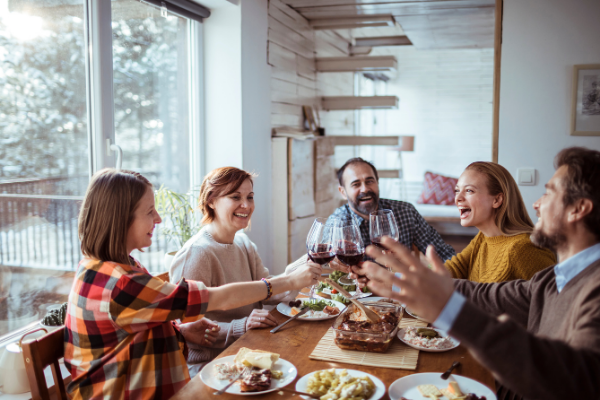 a family sitting at a wooden dining table clinks glasses of wine