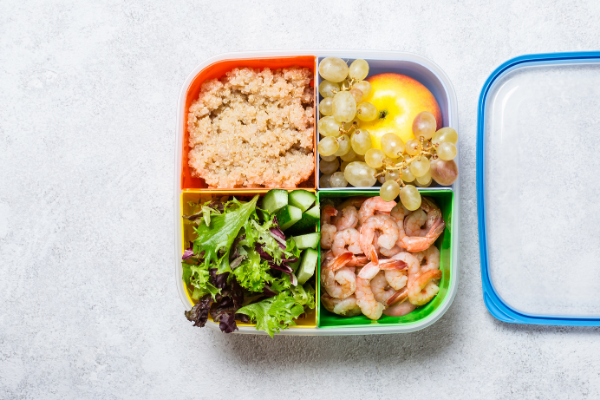 a square plate divided into four quadrants with rice, shrimp, salad and mixed vegetables on it