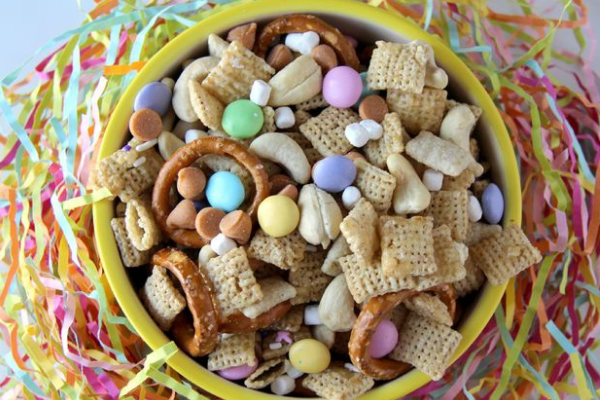 a bowl full of easter chex mix with chex cereal, pretzels, mini marshmalows and mini eggs