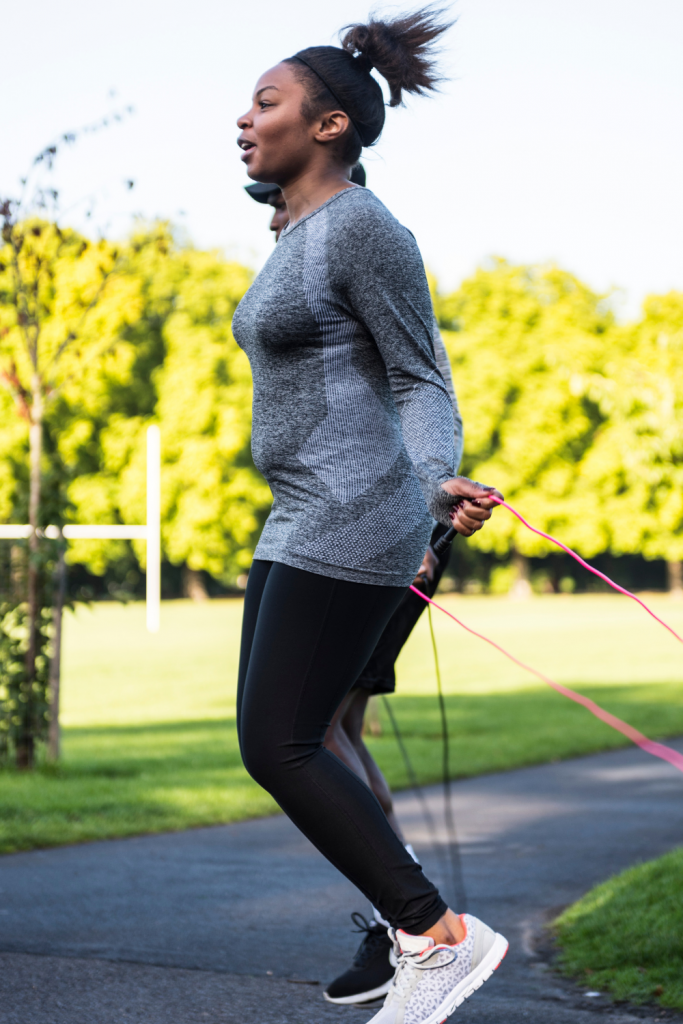 an african american woman with her hair in a ponytail wearing a long grey sweatshirt jumps rope outside