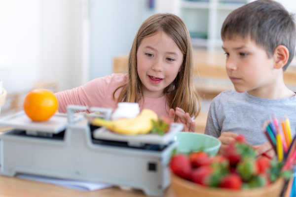 Two young kids weighing foods on a scale in a classroom