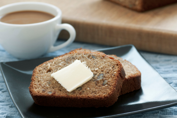 a slice of banana bread with a pat of butter next to a white mug of coffee