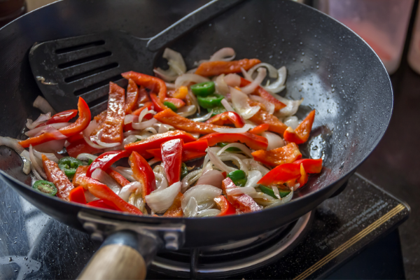 a wok full of beef, peppers and onions stir frying