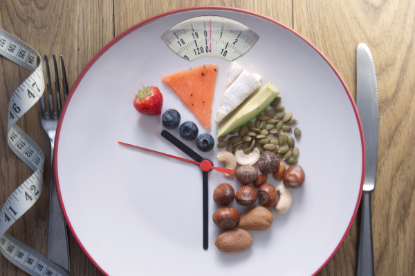 a white plate displays a scate at the top and has food arranged like a clock. between the six and the ten hand is no food, between ten and six are fruit, cheese, vegetables and nuts.