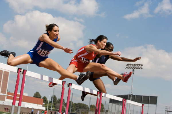 three female hurdlers mid jump with legs extended