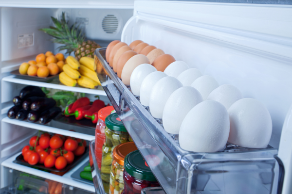 an open regrigerator with eggs and juices on the door shelves and fresh fruits and vegetables on the main shelves