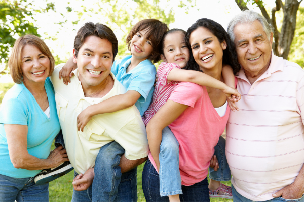 A multi generational family poses for a picture outdoors on a sunny day. The parents hold young kids piggyback and grandparests frame the photo