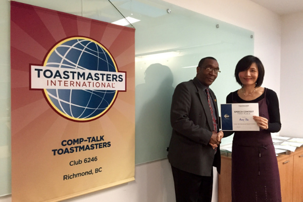 amy yiu being presented with a certificate beside a toastmasters banner