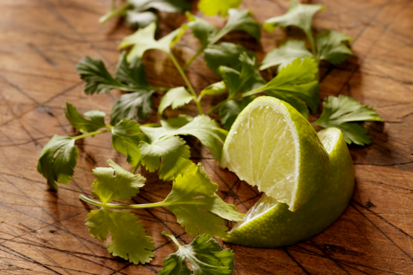 lime wedges and chopped cilantro on a wodden cutting board